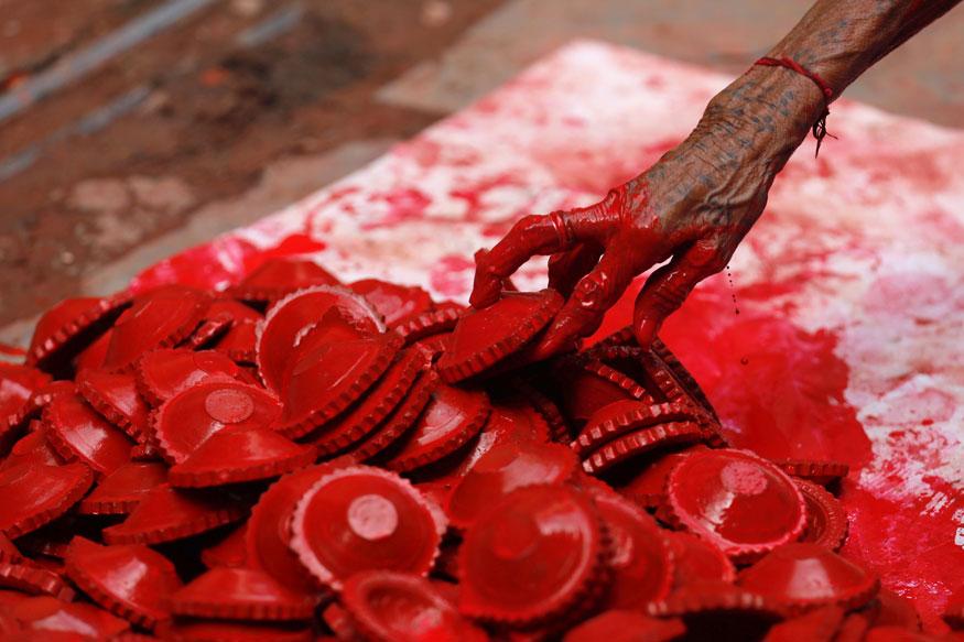 தீபாவளிக்காக தயாரிக்கப்பட்டுள்ள விளக்குகளுக்கு வண்ணம் பூசும் தொழிலாளி. (Image:Reuters)
