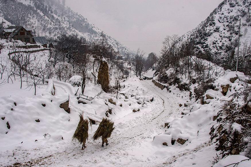 பனி மூடிய சாலையைக் கடந்து செல்லும் மக்கள். (Image: PTI)